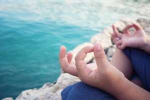 Close up of child meditating and practicing Yoga on the beach.
